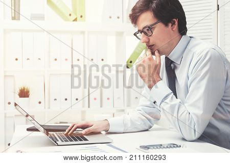 Side view of a young pensive businessman wearing glasses and looking attentively at his laptop screen in office. Toned image