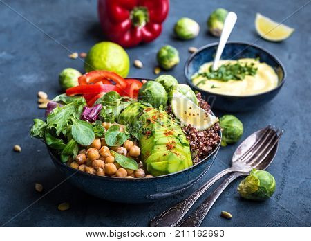 poster of Bowl with healthy salad and dip. Close-up. Buddha bowl with chickpea avocado quinoa seeds red bell pepper fresh spinach brussels sprout lime mix. Vegetarian salad. Clean healthy eating concept