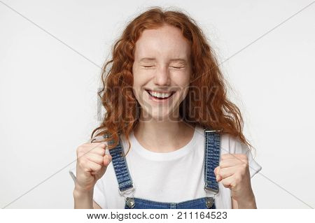 Closeup Of Emotional Redhead Girl Isolated On Gray Background Showing White Teeth While Screaming Wi
