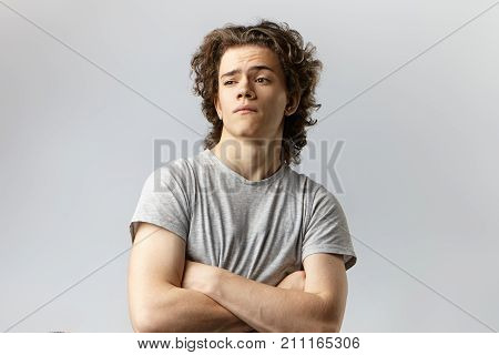Arrogant young Caucasian male with voluminous hair standing in closed posture keeping his arms folded and looking away as if ignoring something expressing indifference insult or displeasure