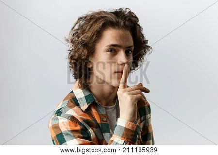People secrecy conspiracy and confidentiality concept. Mysterious young Caucasian male with voluminous hair holding index finger on his lips asking for silence saying: Let's keep it a secret