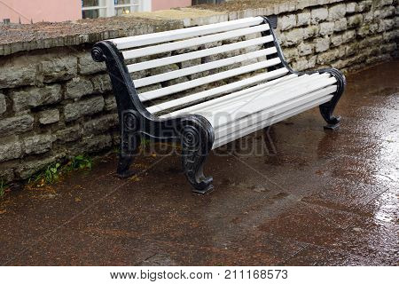 White bench to relax on wet sidewalk