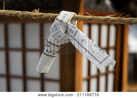 Hiroshima, Japan - May 25, 2017: Close up of a fortune telling paper strip tied up on a rope, omikuji, it is left behind because it predicted not a good fortune