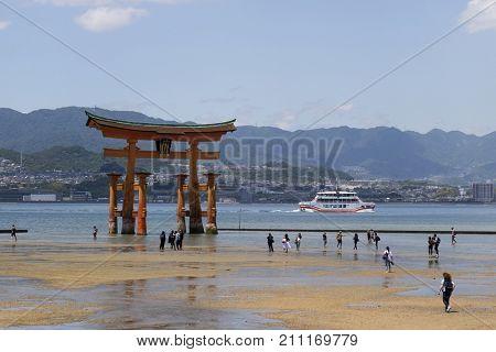 Miyajima - Japan, May 26, 2017: Red Torii gate of the Itsukushima Shrine in the sea at low tide near Miyajima