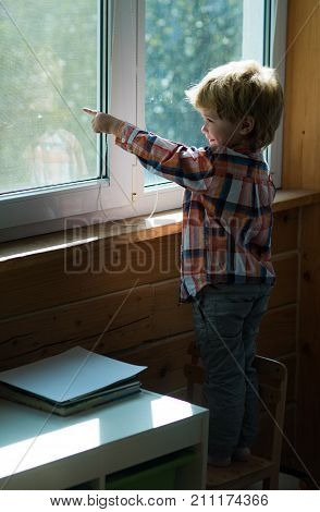 Boy shows finger on something outside window on the street. Beautiful baby blond is standing on chair and looks out of house in the window. Childhood waiting and joy