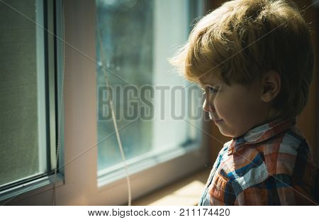 Child waiting parents and looks impatiently in the window. Sad cute boy near the window on a rainy day waiting and hope