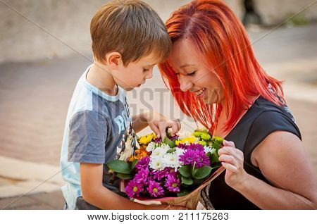 Cute little Caucasian boy handing a flower bouquet to his happy mother. Mother's day illustration.
