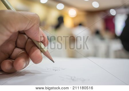 Business people making and writing notes at conference seminar with blur light business peple background.Seminar is form of academic instruction offered by a commercial or professional organizatio