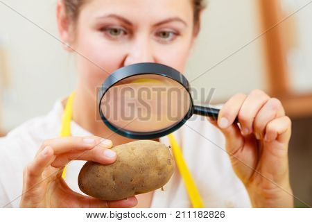 Mature woman female inspecting testing potato food with magnifying glass.