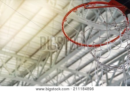 old orange basketball hoop with white net in indoor gymnasium sport metal roof background