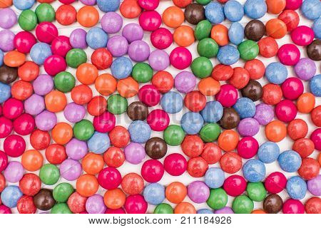 Close up of a pile of colorful chocolate coated candy. Chocolate pattern. Chocolate background