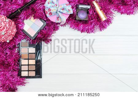 Gift make up, cosmetics and New Year ornaments and toys on white wooden background. Christmas and new year decoration for post card gift. Copy space for text