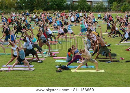 ATLANTA, GA - JULY 2017: Dozens of people stretch doing a yoga pose as they take part in a free group yoga class at the Old Fourth Ward Park in Atlanta GA on July 2 2017.