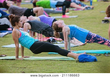 ATLANTA, GA - JULY 2017: Dozens of people do the reverse plank pose as they take part in a free group yoga class at the Old Fourth Ward Park in Atlanta GA on July 2 2017.