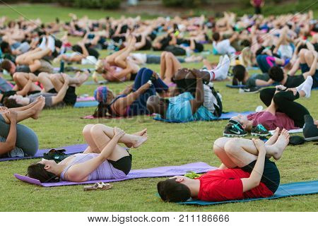 ATLANTA, GA - JULY 2017:  Dozens of people do the wind running pose on their backs as they take part in a free group yoga class at the Old Fourth Ward Park in Atlanta GA on July 2 2017.