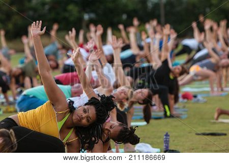 ATLANTA, GA - JULY 2017: Dozens of people do the triangle yoga pose as they take part in a free group yoga class at the Old Fourth Ward Park in Atlanta GA on July 2 2017.