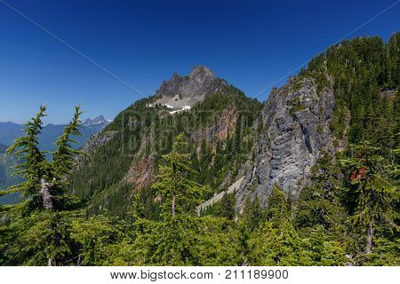 A summer season view of Mount Forgotten as seen along its hiking trail with White Chuck Mountain Peak in the background.