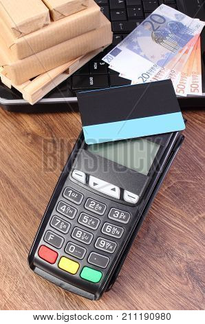Payment Terminal With Credit Card, Currencies Euro, Laptop And Wrapped Boxes On Pallet