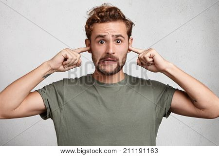 Stressful Man With Trendy Hairdo, Mustache And Beard Plugs Ears, Avoids Loud Sounds At Street, Doesn