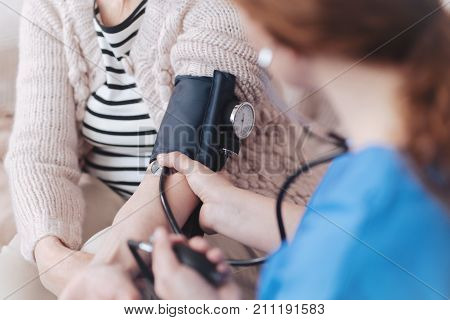 Less worries more positive moments. Close up view on a female nurse sitting in front of a senior patient while measuring her blood pressure during a regular visit.