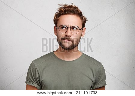 Serious Thoughtful Clever Scientific Worker Wears Spectacles, Has Beard, Curves Lower Lip, Tries To