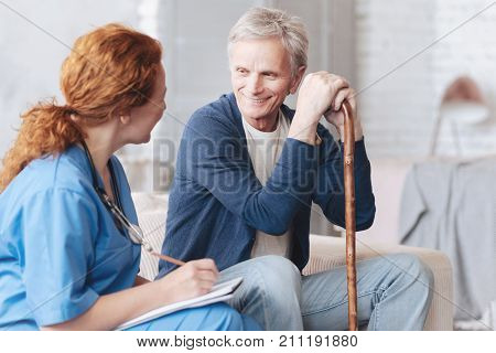 Possitive attitude to patients. Relaxed retired man with a walking stick smiling while sitting on a sofa and talking to a female doctor during a regular visit at home.