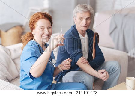 Medical treatment. Positive minded female doctor smiling while sitting next to an elderly male patient and looking at a syringe while preparing for vaccination.
