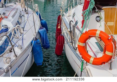 detail of two boats anchored with the typical colored fenders and the characteristic orange life-buoy /two boats anchored at the  harbor