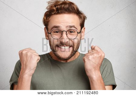 Happy Overjoyed Male Winner Clenches Fists With Enjoyment Can`t Stop His Feelings And Emotions, Clen