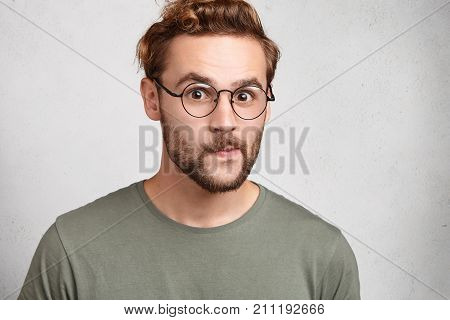 Portrait Of Attractive Young Man Wears Spectacles, Looks In Bewilderment, Stares At Camera, Being Pu