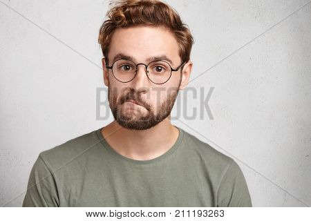 Indoor Shot Of Doubtful Bearded Man In Spectacles, Curves Lips, Looks Directly Into Camera, Hesitate