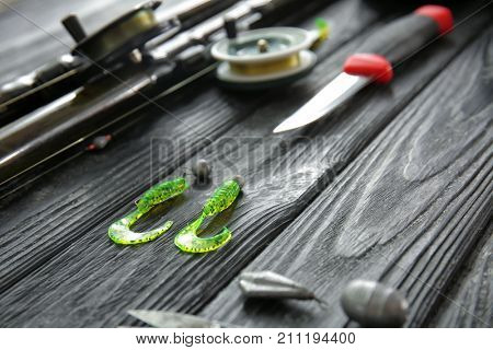 Spoon baits and other fishing equipment on wooden table, closeup
