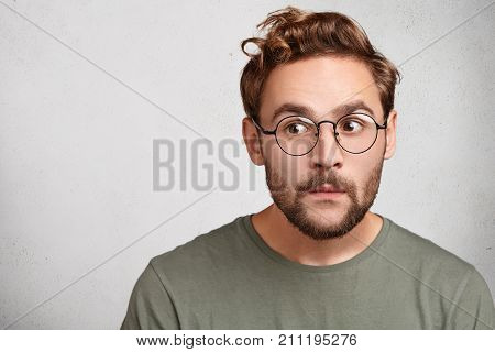 Headshot Of Attractive Stylish Youngster Or Male Wonk Wears Round Spectacles, Looks Curious Aside, T