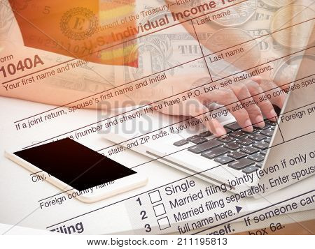 Double Exposure hand typing laptop with US tax form/ taxation concept