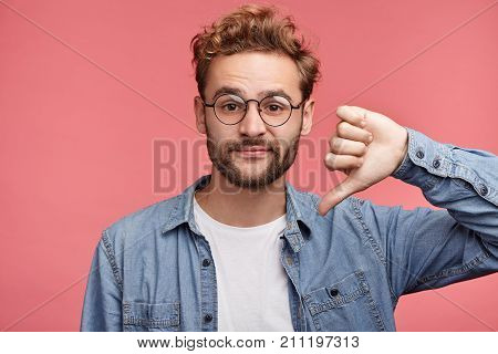 Stylish Fashionable Male Poses Indoors Against Pink Background, Assess Project, Shows Sign Of Dislik