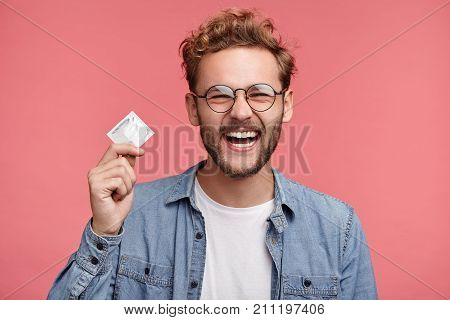 Cheerful Bearded Man Holds Condom, Being Glad To Have Unforgettable Night With Woman, Wants To Repea