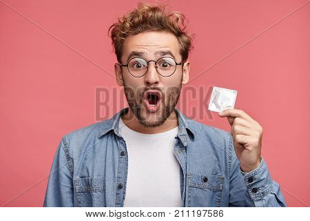 Astonsihed Male Wears Spectacles, Opens Mouth With Great Surprisment As Finds Condom In Bedroom, Doe