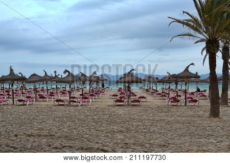 Tropical thatch umbrellas on an deserted beach in a nasty weather
