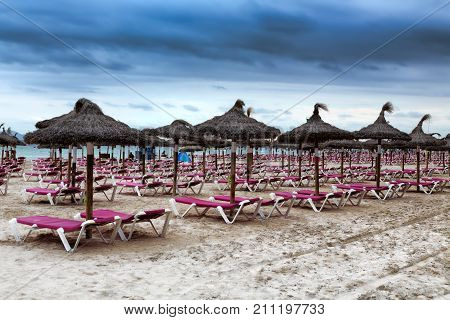 Deserted beach with sun beds and umbrellas