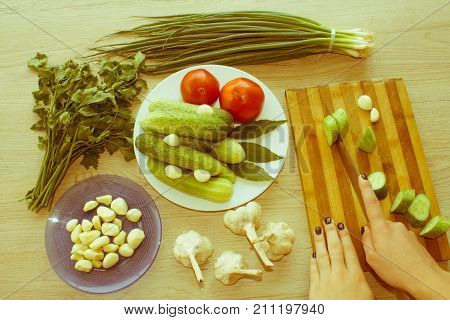Young woman cooking healthy meal in the kitchen. Cooking healthy food at home. Woman in kitchen preparing vegetables. Cropped image of young girl cutting vegetables - Retro color