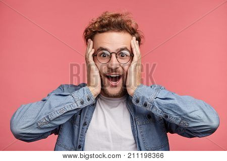 Indoor Shot Of Amazed Excited Man Doesn`t Believe His Success, Keeps Hands On Head, Stares At Camera