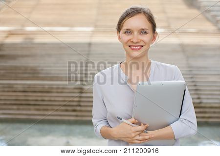 Portrait of successful young Caucasian businesswoman holding laptop, looking at camera and smiling. Success and casual business concept