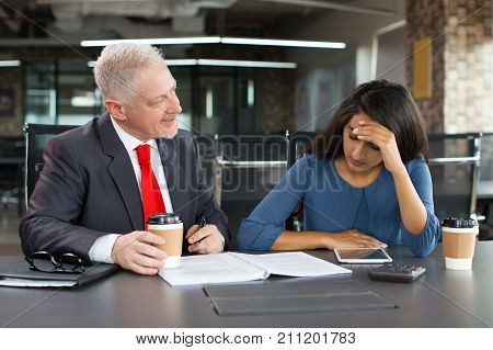 Portrait of displeased senior Caucasian leader sitting at table with coffee and blaming young Indian businesswoman in office. Business relationship and internship concept