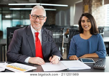 Portrait of cheerful senior Caucasian leader wearing eyeglasses sitting at table with young Indian female employee, writing in register, looking at camera and smiling. Internship and team concept