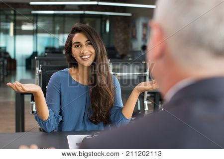 Young Indian businesswoman sitting opposite her boss, shrugging shoulders and smiling at camera. Job interview and ignorance concept