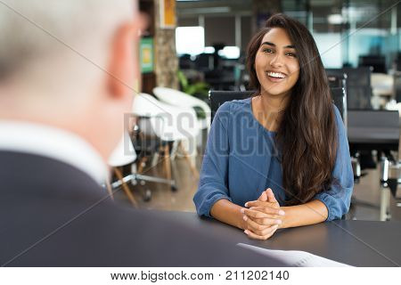 Portrait of young Indian female candidate sitting at table opposite senior executive and laughing at job interview. Recruitment concept