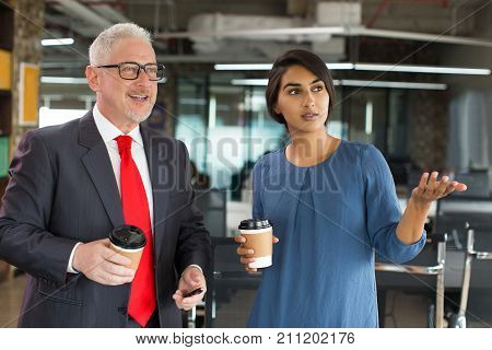 Business assistant presenting new project or office to boss. Cheerful excited senior businessman listening with pleasure to his manager. They discussing plan of work. Work with consultant concept