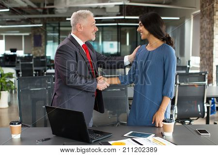 Cheerful employer greeting new worker and shaking hand of young lady congratulating with beginning of career in his company. Business partners concluding deal in office. Business relationship concept