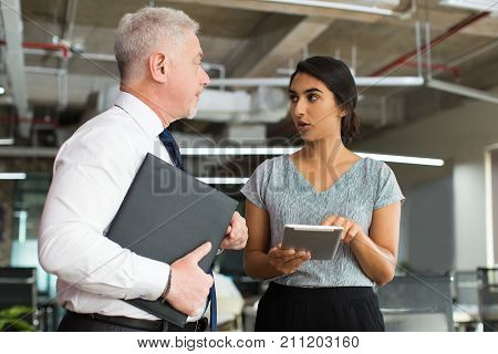 Serious young Hispanic secretary reporting directly to chief using tablet. Senior boss listening to assistants offer in office. Organization concept