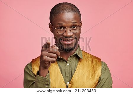 Portrait Of Pleased Dark Skinned Man Wears Shirt And Vest, Points At You, Chooses Someone Or Adverti